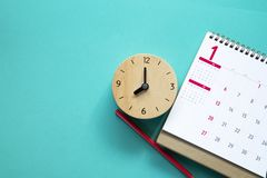 Schließen Sie oben vom Kalender, von der Uhr und vom Bleistift auf dem Tisch lizenzfreies stockbild