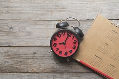 Schließen Sie oben vom Kalender, vom Wecker und vom Bleistift auf dem Tisch stockfotografie