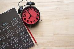 Schließen Sie oben vom Kalender, vom Wecker und vom Bleistift auf dem Tisch lizenzfreies stockbild