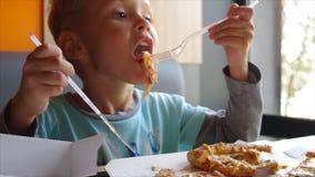 Schließen Sie oben vom kleinen netten Jungen, der Pizza isst Junge mit vier Jährigen, der eine Scheibe der Pizza isst stock footage