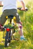 Schließen Sie oben vom Kleinkindjungenreiten auf seinem Fahrrad mit Blumen, draußen Junge, der sein erstes gelbes Fahrrad auf ein Stockfoto