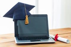 Schließen Sie oben vom Laptop mit Doktorhut und Diplom Stockfotos