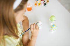 Schließen Sie oben vom Mädchen, das Osterei durch Malerpinsel färbt stockfotos