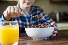 Schließen Sie oben vom Mädchen, das Schüssel zuckerhaltige Frühstückskost aus Getreide in Kitch isst Lizenzfreie Stockfotografie