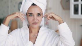 Schließen Sie oben vom Mädchen im Bademantel, mit Tuch auf Kopf tut das Verjüngen von Gesichtsmassage stock footage