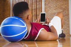 Schließen Sie oben vom männlichen Basketball-Spieler, der Handy verwendet Lizenzfreie Stockbilder