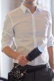Schließen Sie oben vom männlichen Stilisten mit Bürste am Salon Stockfotografie