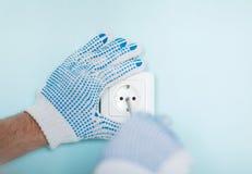 Schließen Sie oben vom Mann in den Handschuhen, die neuen Sockel installieren Lizenzfreies Stockbild