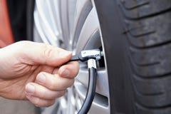 Schließen Sie oben vom Mann, der Auto-Reifen mit Luftdruck-Linie aufbläst Stockfotos