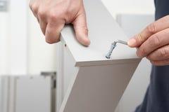 Schließen Sie oben vom Mann, der Flachgehäuse-Möbel zusammenbaut Stockbilder