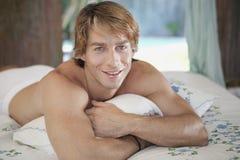 Schließen Sie oben vom Mann, der im Bett lächelt Lizenzfreie Stockbilder