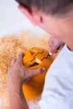 Schließen Sie oben vom Mann, der Kürbis Jack-O-Laterne für Halloween schnitzt Lizenzfreie Stockbilder