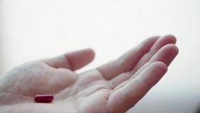 Schließen Sie oben vom Mann, der rote Kapsel-Pille nimmt Medizin, die in der Hand in Zeitlupe fällt stock footage