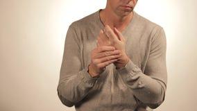 Schließen Sie oben vom Mann, der sein Handgelenk auf weißem Hintergrund massiert Gesundheitswesen- und Problemkonzept stock video