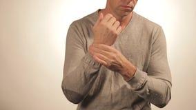 Schließen Sie oben vom Mann, der sein Handgelenk auf weißem Hintergrund massiert Gesundheitswesen- und Problemkonzept stock footage