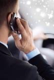 Schließen Sie oben vom Mann, der Smartphone beim Fahren des Autos verwendet Stockfotografie