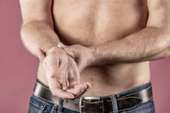 Schließen Sie oben vom Mann, der unter den Schmerz in seinem Handgelenk auf rosa Hintergrund leidet Gesundheitswesen- und Problem lizenzfreie stockbilder