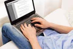 Schließen Sie oben vom Mann, der zu Hause auf Laptop-Computer schreibt Lizenzfreie Stockbilder