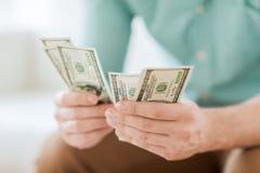 Schließen Sie oben vom Mann, der zu Hause Geld zählt Stockbild
