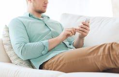 Schließen Sie oben vom Mann, der zu Hause mit Smartphone sitzt Stockfotos