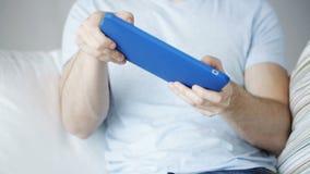 Schließen Sie oben vom Mann, der zu Hause Spiel auf Tabletten-PC spielt stock footage
