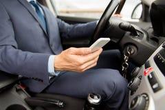 Schließen Sie oben vom Mann mit dem Smartphone, der Auto fährt Lizenzfreies Stockfoto
