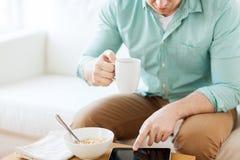 Schließen Sie oben vom Mann mit dem Tabletten-PC, der frühstückt Stockbilder