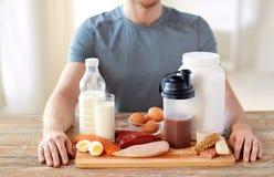 Schließen Sie oben vom Mann mit Lebensmittelreichen im Protein auf Tabelle lizenzfreie stockbilder
