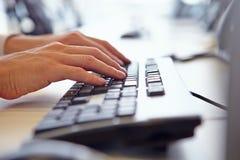 Schließen Sie oben vom Mann? s-Hände unter Verwendung der Tastatur eines Computers stockfotografie