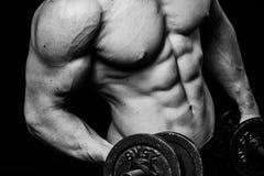 Schließen Sie oben vom muskulösen Bodybuilderkerl, der Übungen mit Gewichtsdummkopf über lokalisiertem schwarzem Hintergrund tut  Lizenzfreies Stockbild