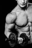 Schließen Sie oben vom muskulösen Bodybuilderkerl, der Übungen mit Gewichtsdummkopf über schwarzem Hintergrund tut Schwarzes und Stockbild
