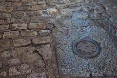 Schließen Sie oben vom nassen alten Steinboden mit Pfützen und Wasserversorgungsabdeckungen Stockbilder