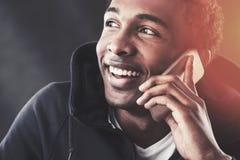 Schließen Sie oben vom netten Afroamerikanermann am Telefon Stockbild