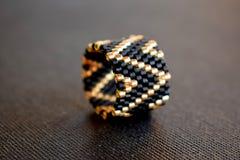 Schließen Sie oben vom perlenbesetzten Ring auf einer schwarzen Tabelle, geometrisches Muster stockbilder