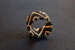 Schließen Sie oben vom perlenbesetzten Ring auf einer schwarzen Tabelle, geometrisches Muster lizenzfreie stockfotografie
