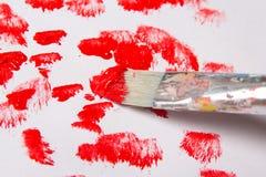 Schließen Sie oben vom Pinsel mit roten Farbenanschlägen über Weiß Stockbild