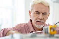 Schließen Sie oben vom reizend älteren Mann, der mit Drucker 3D arbeitet stockfoto