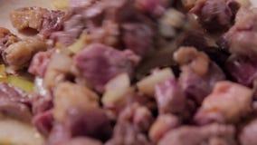 Schließen Sie oben vom Rindfleisch, das in der Bratpfanne mit Zwiebel und Knoblauch gebraten wird stock footage