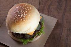 Schließen Sie oben vom Rindfleischburger mit Käse auf hölzerner Tabelle Stockfotos