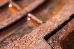 Schließen Sie oben vom rostigen Metallkanaldeckel mit Wasser Stockfoto