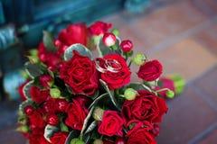 Schließen Sie oben vom roten Hochzeitsblumenstrauß mit goldenem Ring Stockfoto