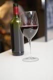 Schließen Sie oben vom Rotwein in Glas vor der Flasche Stockbild