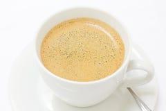 Schließen Sie oben vom sahnigen Kaffee in einem weißen Cup lizenzfreie stockfotografie