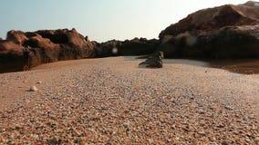Schließen Sie oben vom Sand auf dem nassen Strand, Felsen im Hintergrund, kleines Seepool rechts Schuss durch nasse Kamera mit Tr stock video footage