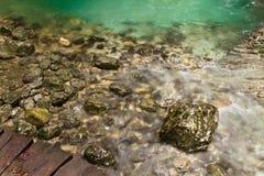 Schließen Sie oben vom schönen Bronzefelsen im reinen haarscharfen grünen Wasser Stockfotos