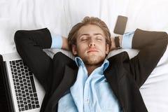 Schließen Sie oben vom schönen jungen Manager in der noblen Klage, die im Bett mit den Händen unter Kopf liegt, schlafen Sie mit  Stockfoto