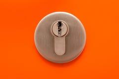 Schließen Sie oben vom Schlüsselloch auf orange Tür Lizenzfreies Stockfoto