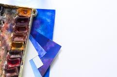 Schließen Sie oben vom Schreibtisch mit Papier, Aquarell und Bürsten Vielzahlfarben Stockfotografie