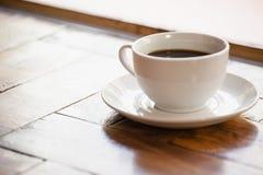 Schließen Sie oben vom schwarzen Kaffee in der Schale auf Holztisch Lizenzfreie Stockbilder