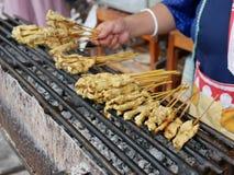 Schließen Sie oben vom Schweinefleischgrill Moo Satay, der auf einem Holzkohlengrill gebraten wird stockfotos